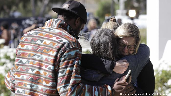 Mourners embrace outside of the Thousand Oaks Teen Center
