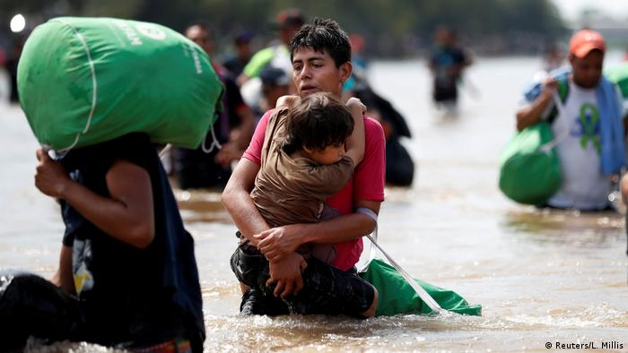 A young man holds a child while crossing a river on their way to the US