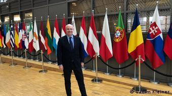 Уильям Браудер на фоне флагов стран-членов ЕС