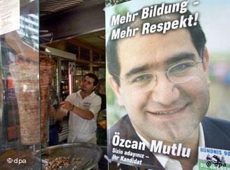 Ein Wahlplakat des türkisch-stämmigen Özcan Mutlu (Bündnis 90/Die Grünen) zur Wahl des Abgeordnetenhauses von Berlin am 17. September hängt am Montag (14.08.2006) in Berlin am Fenster eines Döner-Kebap Restaurants. Mutlu, der für den Bezirk Kreuzberg-Friedrichshain kandidiert, hat auf seinem Plakat die Worte Ihr Kandidat auf türkisch und deutsch gedruckt. Foto: Gero Breloer dpa/lbn +++(c) dpa - Report+++