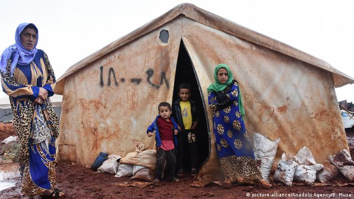 A family outside their makeshift tent at the Al-Ihsan camp. Esref Musa / Anadolu Agency