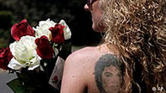 With a Michael Jackson tattoo on her back, Svenja Maniak from Berlin, Germany, holds flowers while waiting outside the Jackson family home in the Encino section of Los Angeles Thursday Sept. 3, 2009. The funeral for Michael Jackson will be a private family ceremony set for Thursday night inside the massive multistory building at star-studded Forest Lawn Glendale cemetery. (AP Photo/Nick Ut)