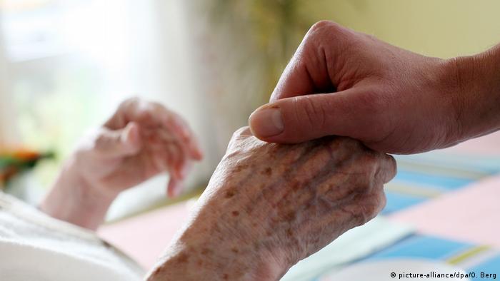 Медсестра держит за руку больного человека