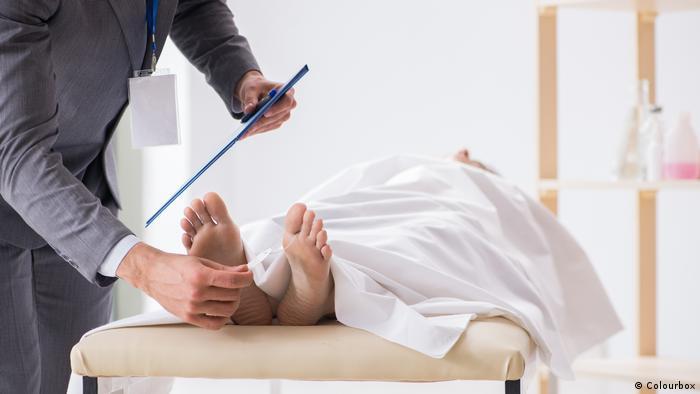 Corpo sendo examinado por legista em necrotério