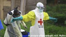 ARCHIV - 09.09.2018, Kongo, Beni: Ein Mitarbeiter des Gesundheitsamtes sprüht nach einem Einsatz in einem Ebola-Behandlungszentrum Desinfektionsmittel auf einen Mitarbeit des Roten Kreuzes. (zu dpa «Ebola-Virus breitet sich weiter aus - Uganda beginnt Ebola-Impfungen» vom 02.11.2018) Foto: Al-Hadji Kudra Maliro/AP/dpa +++ dpa-Bildfunk +++ |