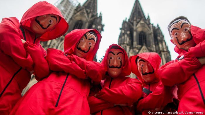 أشخاص يرتدون أزياء مسلسل 'لاكاسا دي بابيل الذي سرق أبطاله بنكا مركزيا إسبانيا