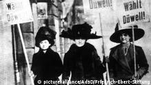 HANDOUT - 24.10.2018, ---: Die Aufnahme aus dem Januar 1919 zeigt drei Unterstützerinnen der Unabhängigen Sozialdemokratischen Partei Deutschlands (USPD) mit Transparenten auf denen steht «Wählt Düwell!». Die Frauen unterstützen den USPD-Kandidaten Bernhard Düwell der 1919 in die Weimarer Nationalversammlung und 1920-1924 in den Reichstag gewählt wurde. Innerhalb der USPD gehörte er zum linken Flügel, welcher sich Ende 1920 mit der KPD zusammenschloss, der auch Düwells Vater schon seit 1919 angehörte. (zu dpa 100 Jahre Frauenwahlrecht vom 10.11.2018) Foto: --/AdsD/Friedrich-Ebert-Stiftung/dpa - ACHTUNG: Nur zur redaktionellen Verwendung und nur mit vollständiger Nennung des vorstehenden Credits +++ dpa-Bildfunk +++  