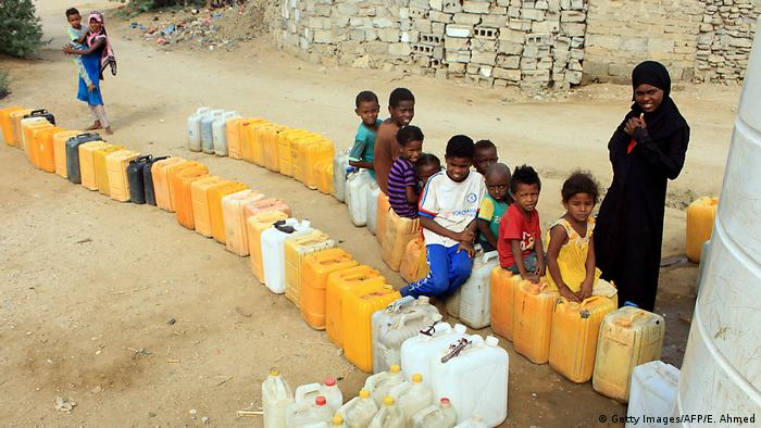 Displaced children waiting for water in a camp in Hajjah province