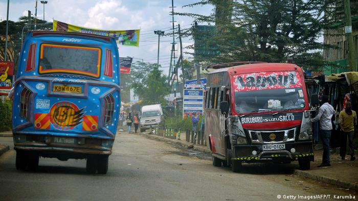 Minibus taxis known as Matatus drop off passengers on a street in Nairobi