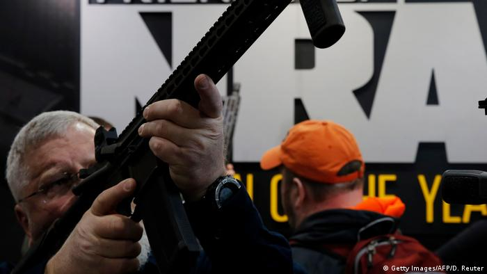 A man aims a gun in front of an NRA stand