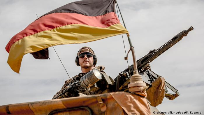 A soldier in Mali posing with a machine gun under the German flag