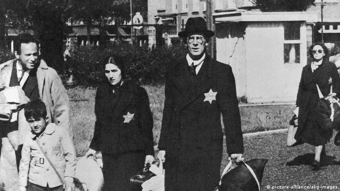 Foto histórica com pessoas de estrela judia no peito carregando malas