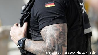 A policeman sports a tattoo on his arm (picture alliance/AP Photo/M. Sohn)