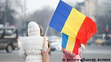 Two protesters hold Romanian flags in front of government headquarters (picture-alliance/J. Arriens)