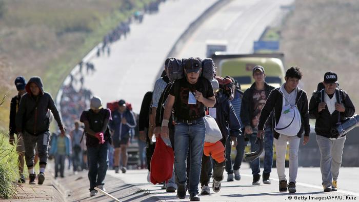 Foto de migrantes na fronteira entre EUA e México