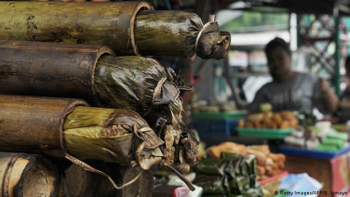 Hollow bamboo stalks containing food wrapped in leaves
