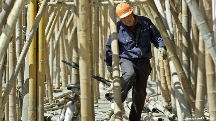 A man walking between bamboo trunks