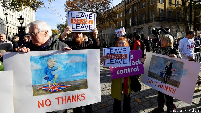 Demonstrators hold banners as they protest at the entrance to Downing Street