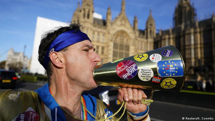 A protester with a megaphone in front of parliament in the UK. (Reuters/K. Coombs)