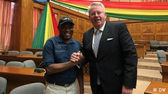 Limbourg shaking hands with a Ghanain man in a room adorned with the Ghanaian flag