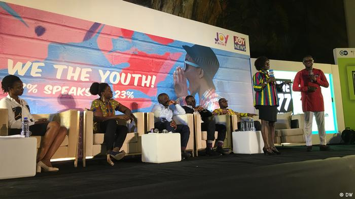 Two women and three men are seated behind the debate hosts and a large banner with the words We the youth