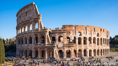 Crowds stand outside the Colosseum in Rome, Italy