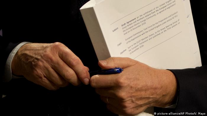 EU chief Brexit negotiator Michel Barnier holds the draft withdrawal agreement during a media conference in Brussels