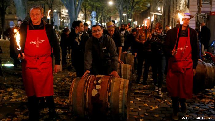 Männer rollen in Lyon anlässlich des Verkaufstarts des Beaujolais Nouveau Fässer über die Straße. (Reuters/E. Foudrot)