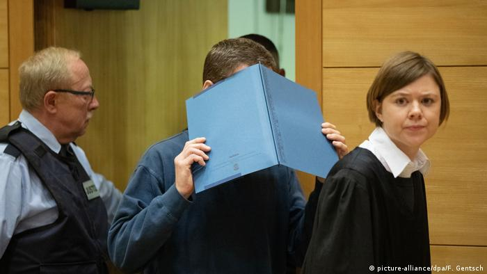 The suspect enters the courtroom hiding his face behind a folder