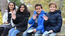 Schoolchildren of diverse backgrounds smiling for a picture in Germany (picture-alliance/dpa/A. Dedert)