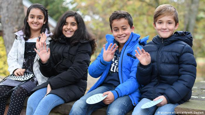 Schoolchildren of diverse backgrounds smiling for a picture in Germany