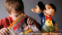 Ein Junge liest in einem Micky-Maus-Heft. Neben ihm steht eine Micky-Maus-Figur.