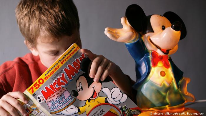 Boy reading Mickey Mouse comic in German (picture-alliance/dpa/U. Baumgarten)