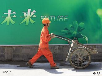 In this June 25, 2009 photo, a migrant worker pushes a cart at a construction site in Shanghai, China. China has seen a rebound in the employment of migrant workers, with 150 million employed outside their hometown by the end of June, a Chinese official said Friday. The financial crisis hit China's export sector hard, sending more than 20 million migrant workers back to the countryside from their jobs in coastal areas, the government reported in February. (AP Photo/Eugene Hoshiko)