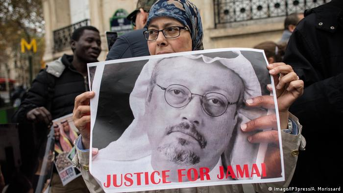 A woman holds a poster calling for justice in the slaying of Jamal Khashoggi