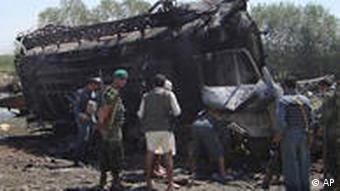 The site of the NATO airstrike with officials inspecting a completely destroyed fuel truck
