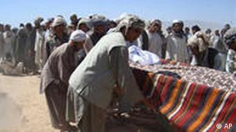Afghani people bury the victims of the NATO air strike in a mass grave near Kunduz, Afghanistan
