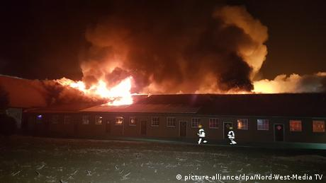 Fire fighters running outside a barn