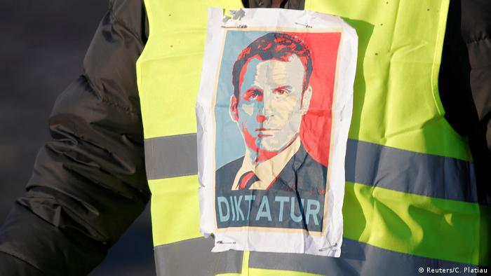 A yellow vest demonstrator has a picture of Macron on it with the word, 'dictator' under his face (Reuters/C. Platiau)