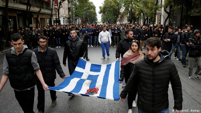 A group of demonstrators carries a Greek flag with carnations placed on it (Reuters/C. Baltas)