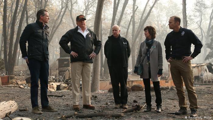 Donald Trump and Jerry Brown stand with others in the charred remains of Paradise