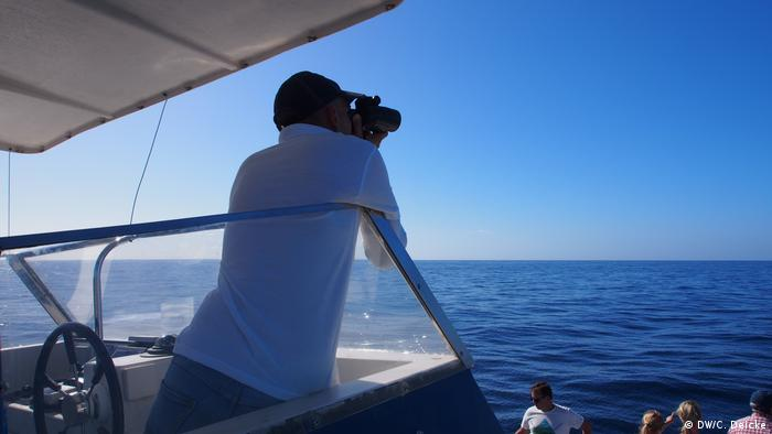 Skipper Ivan López searches the sea with his binoculars