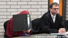 ARCHIV - 19.09.2018, Baden-Württemberg, Baden-Baden: Ein 34 Jahre alter angeklagter Schwimmlehrer (l), dem vorgeworfen wird sich an kleinen Mädchen vergangen zu haben, wartet im Landgericht Baden-Baden mit einem Aktenordner vor dem Gesicht zusammen mit seinem Anwalt Christian Süß auf den Prozessbeginn. Dem Angeklagten wird zur Last gelegt, die zwischen vier und zwölf Jahre alten Kinder während des Schwimmunterrichts zum Teil schwer sexuell missbraucht, genötigt und bedroht zu haben. (zu dpa: «Plädoyers und Urteil im Missbrauchsprozess gegen einen Schwimmlehrer» vom 19.11.2018) Foto: Uli Deck/dpa +++ dpa-Bildfunk +++   Verwendung weltweit