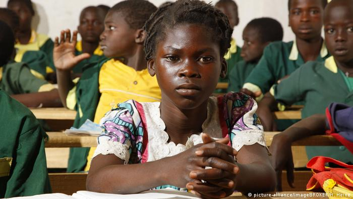 A Cameroonian schoolgirl sitting in a full classroom