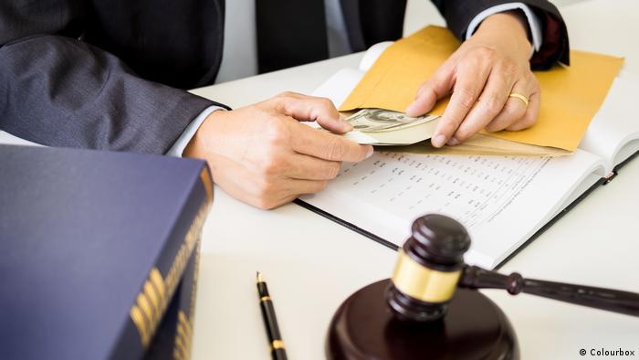Мужчина достает пачку долларов из конверта, рядом лежит судейский молоток