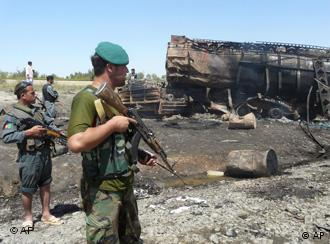 Afghan security forces stand guard near a burnt fuel tanker