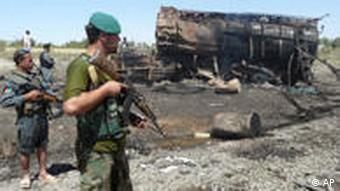 Afghan security forces guarding the fuel tanker wreckage in Kunduz