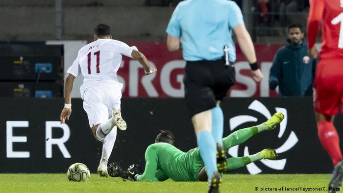 O atacante Akram Afif dribla o goleiro Yvon Mvogo para marcar o gol da vitória do Catar contra a Suíça