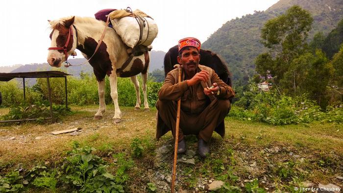 Un hombre sentado en el suelo en las montañas. Al fondo, se ve su caballo.