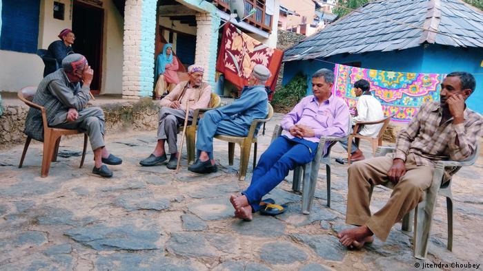 Cinco hombres sentados en sillas de plástico en la plaza del pueblo.